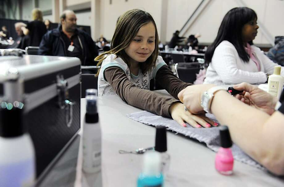 Mikayla Collins, 8, center, has her nails done during the 5th annual Vanderburgh Homeless Connect event at The Centre in Evansville, Ind. on Thursday, March 21, 2013.  Collins and her family came to Homeless Connect last year and were able to find housing with the help of the Evansville Housing Authority, which has a booth at the event.(AP Photo/The Evansville Courier & Press, Molly Bartels) Photo: Molly Bartels, Associated Press