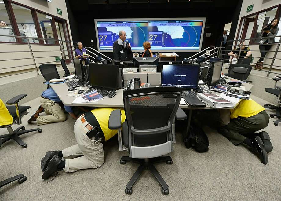 Los Angeles County officials take cover under their desk during a simulated magnitude 7.0 aftershock following a simulated 7.8 magnitude earthquake during a functional exercise at the Los Angeles County Emergency Operations Center (CEOC) hosted by The County of Los Angeles Office of Emergency Management on March 21, 2013 in Los Angeles, California. The training exercise featured the California Integrated Seismic Network's Earthquake Ready Warning Demonstration System, which included 88 cities, 137 unincorporated communities, 200 schools and several nonprofit organizations.  (Photo by Kevork Djansezian/Getty Images) Photo: Kevork Djansezian, Getty Images