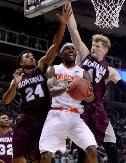 C.J. Fair #5 of the Syracuse Orange drives to the basket against Spencer Coleman #24 and Eric Hutchi