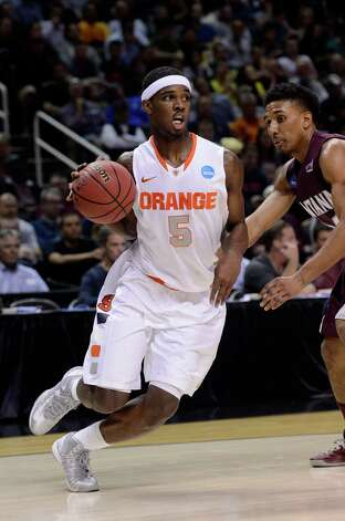 C.J. Fair #5 of the Syracuse Orange handles the ball against Spencer Coleman #24 of the Montana Grizzlies in the first half during the second round. Photo: Thearon W. Henderson, Getty Images / 2013 Getty Images