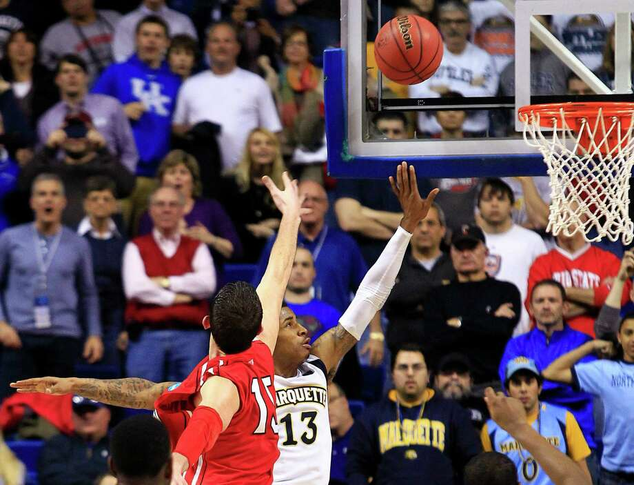 Marquette guard Vander Blue (13) scores the winning basket against Davidson forward Jake Cohen (15) in the final second of their second-round NCAA college basketball tournament game, Thursday, March 21, 2013, in Lexington, Ky. Marquette won 59-58. (AP Photo/James Crisp) Photo: James Crisp