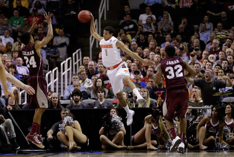 Michael Carter-Williams #1 of the Syracuse Orange jumps to save the ball from going out of bounds against Spencer Coleman #24 and Kareem Jamar #32 of the Montana Grizzlies in the first half. Photo: Ezra Shaw, Getty Images / 2013 Getty Images