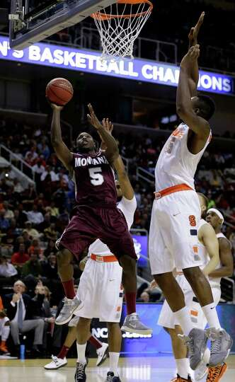 Will Cherry #5 of the Montana Grizzlies drives to the basket against Rakeem Christmas #25 of the Syr