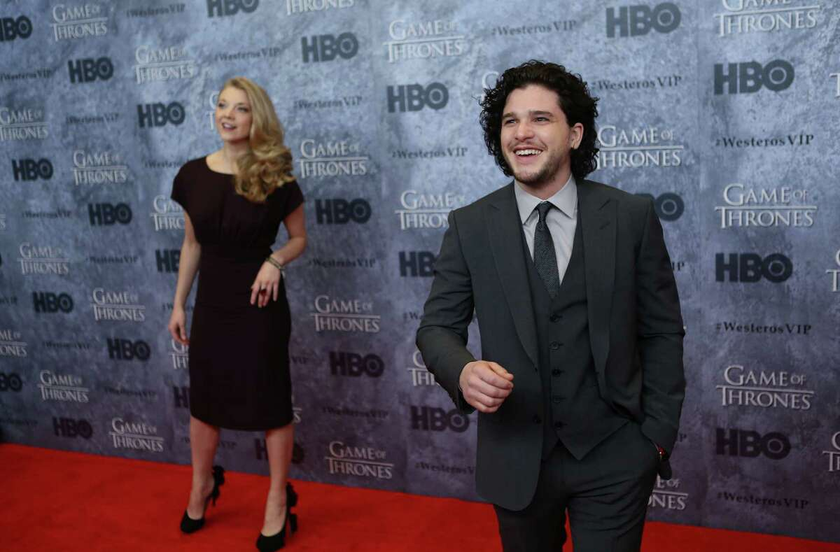 Natalie Dormer, who plays Margaery Tyrell, and Kit Harrington, who plays Jon Snow, react to fans as they walk the red carpet during the Seattle premiere of season three of HBO's Game of Thrones at Seattle's Cinerama. Cast members attended a VIP screening at Cinerama and an after party at the Experience Music Project on Thursday, March 21, 2013.