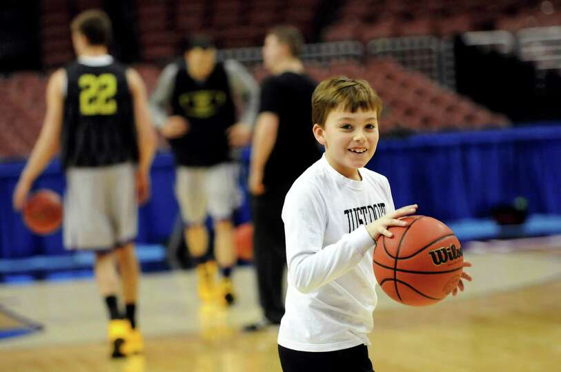Jackson Brown, 10, son of coach Will Brown, plays hoops with the UAlbany team during the NCAA Tourna