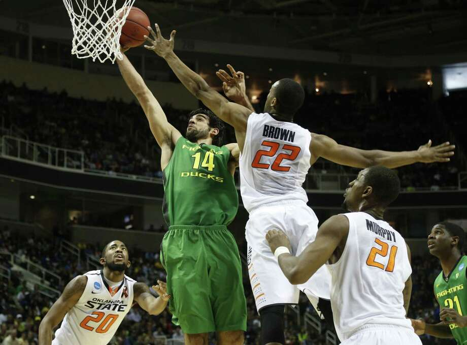 Oregon's Arsalan Kazemi (left) goes to the basket as Oklahoma State's Markel Brown tries to defend in the first half Thursday. Kazemi had 11 points and 17 rebounds in the Ducks' victory. Photo: Josie Lepe / McClatchy-Tribune News Service