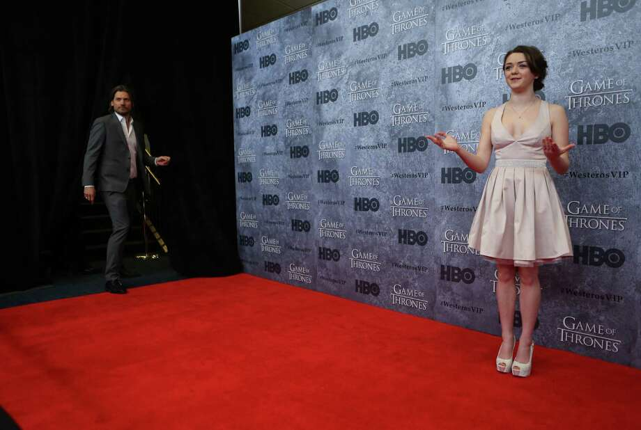 Maisie Williams, who plays Arya Stark, walks the red carpet as Actor Nikolaj Coster-Waldau, who plays Jaime Lannister, emerges during the Seattle premiere of season three of HBO's Game of Thrones at Seattle's Cinerama. Cast members attended a VIP screening at Cinerama and an after party at the Experience Music Project on Thursday, March 21, 2013. Photo: JOSHUA TRUJILLO / SEATTLEPI.COM