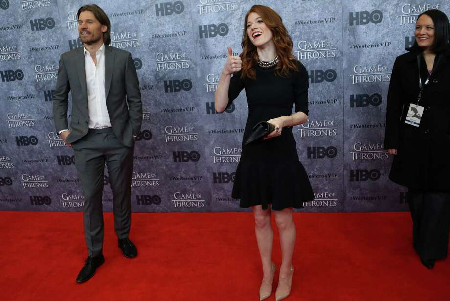 Actor Nikolaj Coster-Waldau, who plays Jaime Lannister, left, and Rose Leslie, who plays Ygritte, give a fan a thumbs up on the red carpet during the Seattle premiere of season three of HBO's Game of Thrones at Seattle's Cinerama. Cast members attended a VIP screening at Cinerama and an after party at the Experience Music Project on Thursday, March 21, 2013. Photo: JOSHUA TRUJILLO / SEATTLEPI.COM