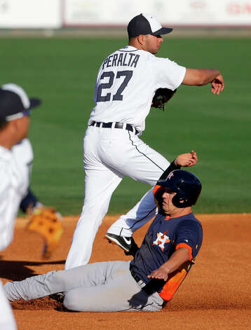 Tigers shortstop Jhonny Peralta (27) throws to first as Brandon Laird slides in. Photo: Carlos Osorio, Associated Press / AP