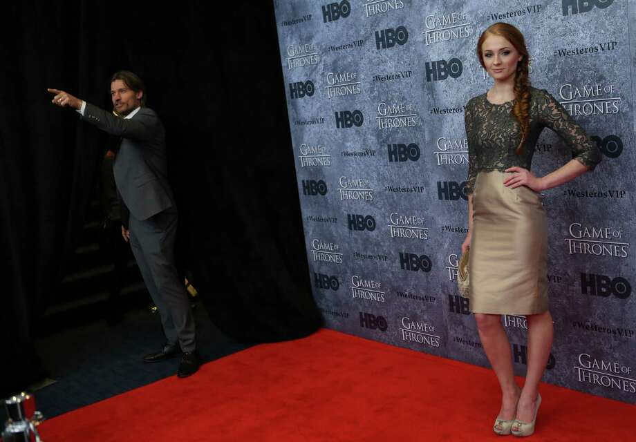 Sophie Turner, who plays Sansa Stark, poses on the red carpet as Nikolaj Coster-Waldau, who plays Jaime Lannister, acknowledges fans during the Seattle premiere of season three of HBO's Game of Thrones at Seattle's Cinerama. Cast members attended a VIP screening at Cinerama and an after party at the Experience Music Project on Thursday, March 21, 2013. Photo: JOSHUA TRUJILLO / SEATTLEPI.COM