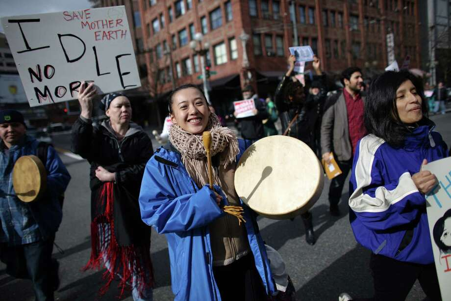 "Protesters march through downtown Seattle during an ""Idle No More"" rally and march on Thursday, March 21, 2013 in Seattle. The group was protesting the proposed export of coal to Asia. The group marched from Westlake Park to Seattle's Harbor Island. ""Idle No More"" is a growing movement among Native Americans that started in Canada. They ask for respect of indigenous rights and treaties and hope to stop projects that could harm the environment. Photo: JOSHUA TRUJILLO / SEATTLEPI.COM"