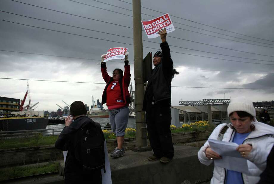 """Participants hold up signs on Seattle's Harbor Island during an """"Idle No More"""" rally and march on Thursday, March 21, 2013 in Seattle. The group was protesting the proposed export of coal to Asia. The group marched from Westlake Park to Seattle's Harbor Island. """"Idle No More"""" is a growing movement among Native Americans that started in Canada. They ask for respect of indigenous rights and treaties and hope to stop projects that could harm the environment. Photo: JOSHUA TRUJILLO / SEATTLEPI.COM"""
