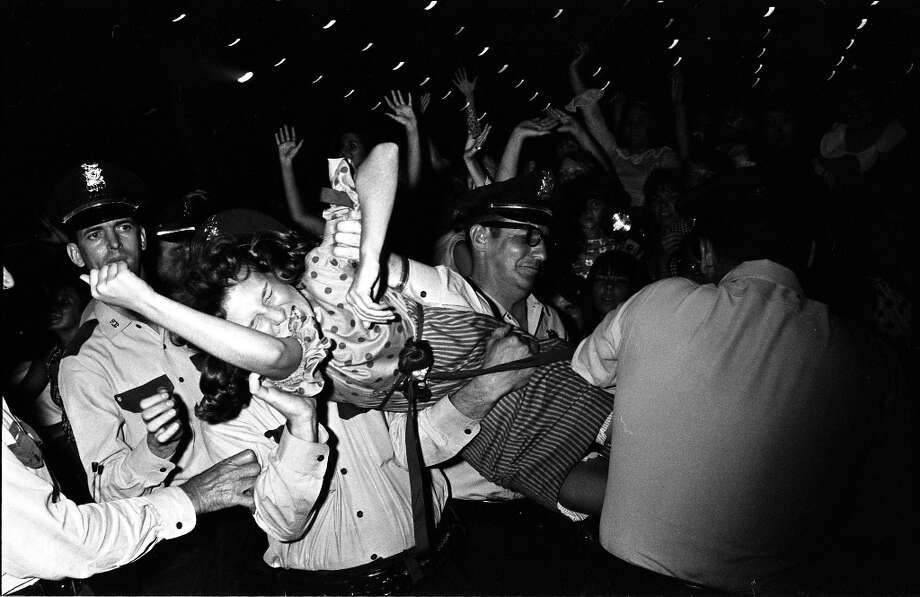 A concert goer is carried off by Houston Police during the Beatles concert at the Sam Houston Coliseum, Houston, Texas, Aug. 19, 1965. Photo: Chronicle File