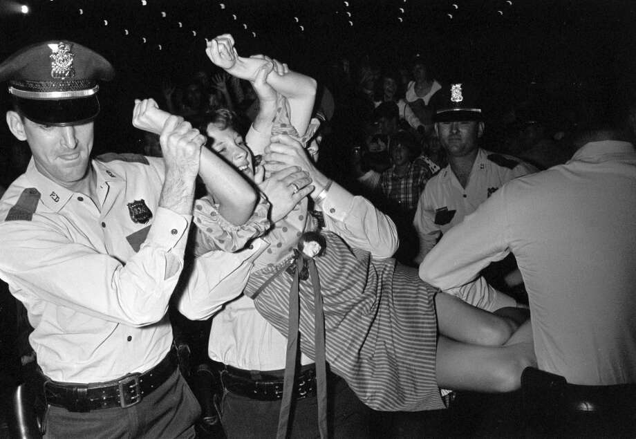 A Beatles fan is carried off by police during the Fab Four's performance at the Coliseum, August 19, 1965. Photo: Curtis McGee, Houston Chronicle / Houston Chronicle