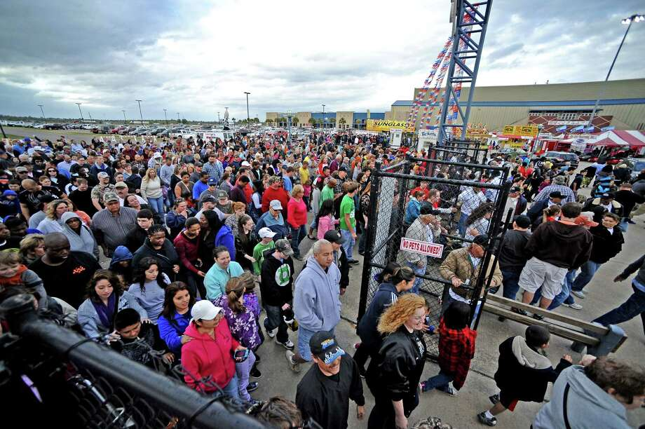 Patrons rush the gates after the opening ceremonies of  the 70th Annual YMBL Southeast Texas State Fair in Beaumont that opened up Thursday, March 21, 2013. Photo taken: Randy Edwards/The Enterprise Photo: Randy Edwards
