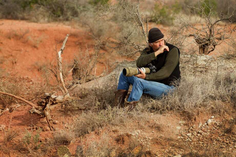 Texas photographer Wyman Meinzer uses a coyote call at the ranch where his father was a cowboy. (More: The state photographer has seen it all) Photo: Brett Coomer, Houston Chronicle / © 2013 Houston Chronicle