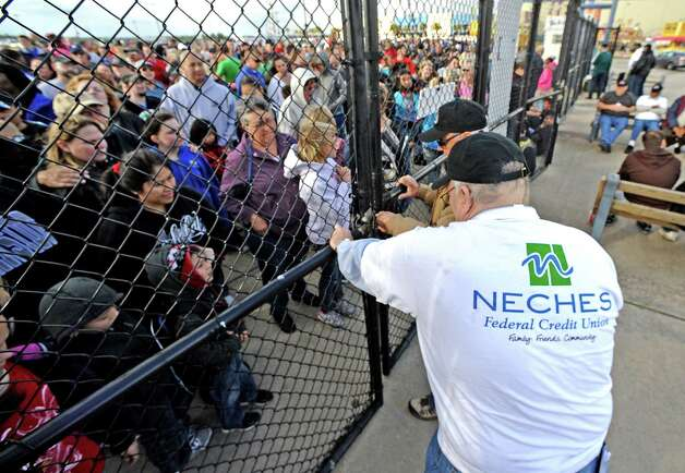 YMBL worker Tom Sachitano opens the gates after the opening ceremonies of  the 70th Annual YMBL Southeast Texas State Fair in Beaumont that opened up Thursday, March 21, 2013. Photo taken: Randy Edwards/The Enterprise
