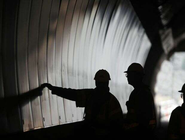 Construction workers inspect the tunnel's southbound bore in January 2012. Caltrans came around and approved building the tunnel after voters supported it in 1996.
