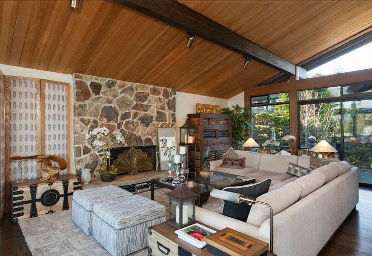 Living room of 5634 39th Ave. W. The 3,220-square-foot modern home, built in 1968, has a Japanese gate and garden, four bedrooms, three bathrooms, a family room, vaulted, exposed wood ceilings, walls of windows, decks and patios, 60 feet of beach frontage and views of boats and ships headed to and from the Ballard locks on a 9,605-square-foot lot. It's listed for $2.4 million.