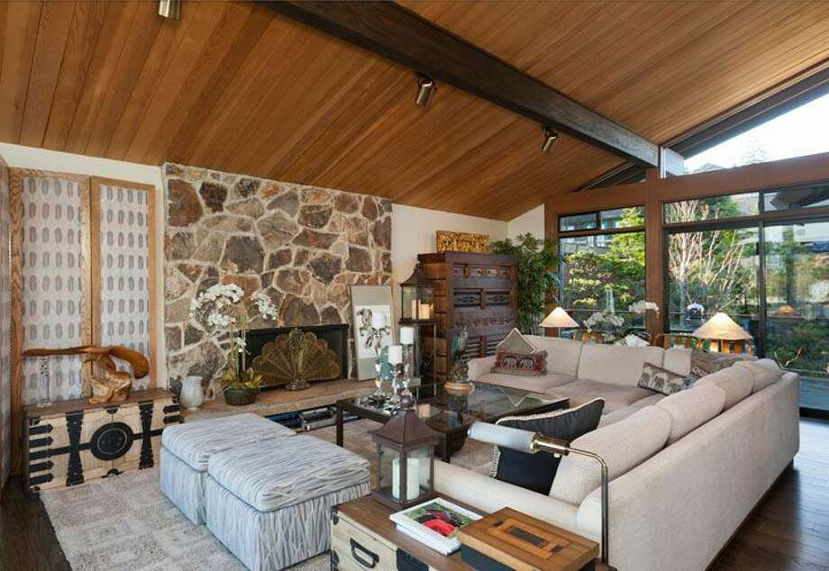 Living room of 5634 39th Ave. W. The 3,220-square-foot modern home, built in 1968, has a Japanese gate and garden, four bedrooms, three bathrooms, a family room, vaulted, exposed wood ceilings, walls of windows, decks and patios, 60 feet of beach frontage and views of boats and ships headed to and from the Ballard locks on a 9,605-square-foot lot. It's listed for $2.4 million. Photo: Courtesy Carol Ard/Windermere Real Estate