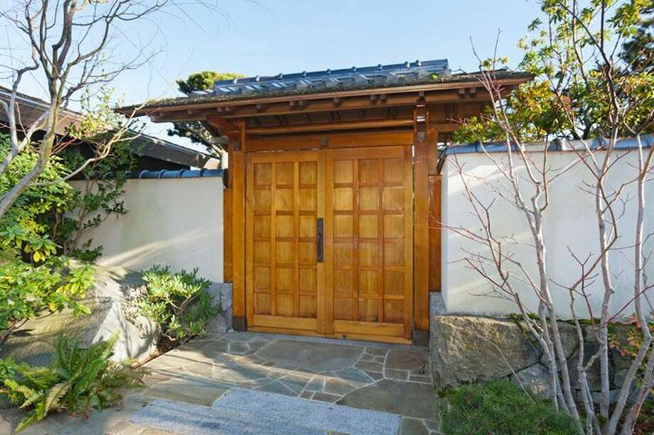 Japanese gate of 5634 39th Ave. W. The 3,220-square-foot modern home, built in 1968, has four bedrooms, three bathrooms, a family room, vaulted, exposed wood ceilings, walls of windows, decks and patios, 60 feet of beach frontage and views of boats and ships headed to and from the Ballard locks on a 9,605-square-foot lot. It's listed for $2.4 million. Photo: Courtesy Carol Ard/Windermere Real Estate