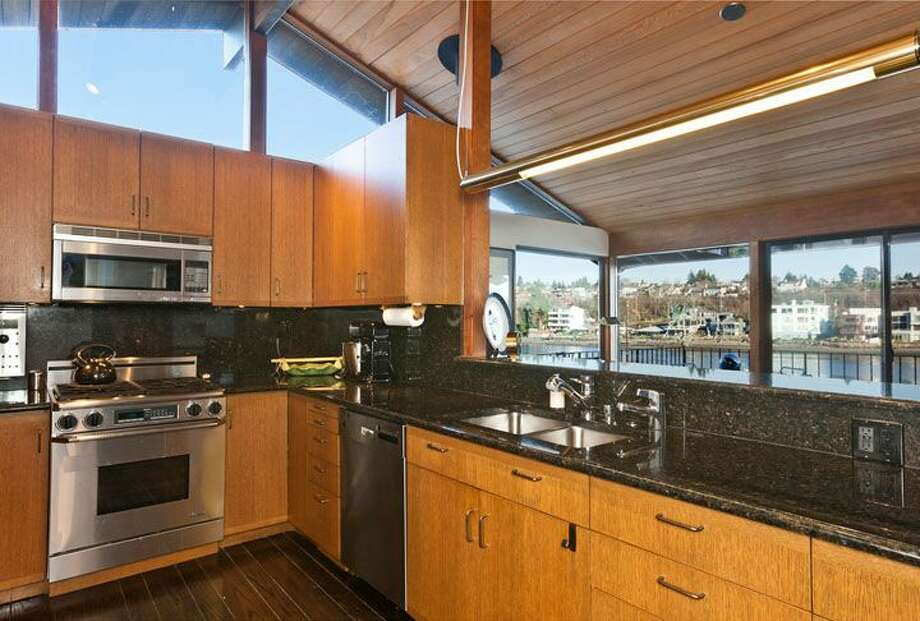 Kitchen of 5634 39th Ave. W. The 3,220-square-foot modern home, built in 1968, has a Japanese gate and garden, four bedrooms, three bathrooms, a family room, vaulted, exposed wood ceilings, walls of windows, decks and patios, 60 feet of beach frontage and views of boats and ships headed to and from the Ballard locks on a 9,605-square-foot lot. It's listed for $2.4 million. Photo: Courtesy Carol Ard/Windermere Real Estate