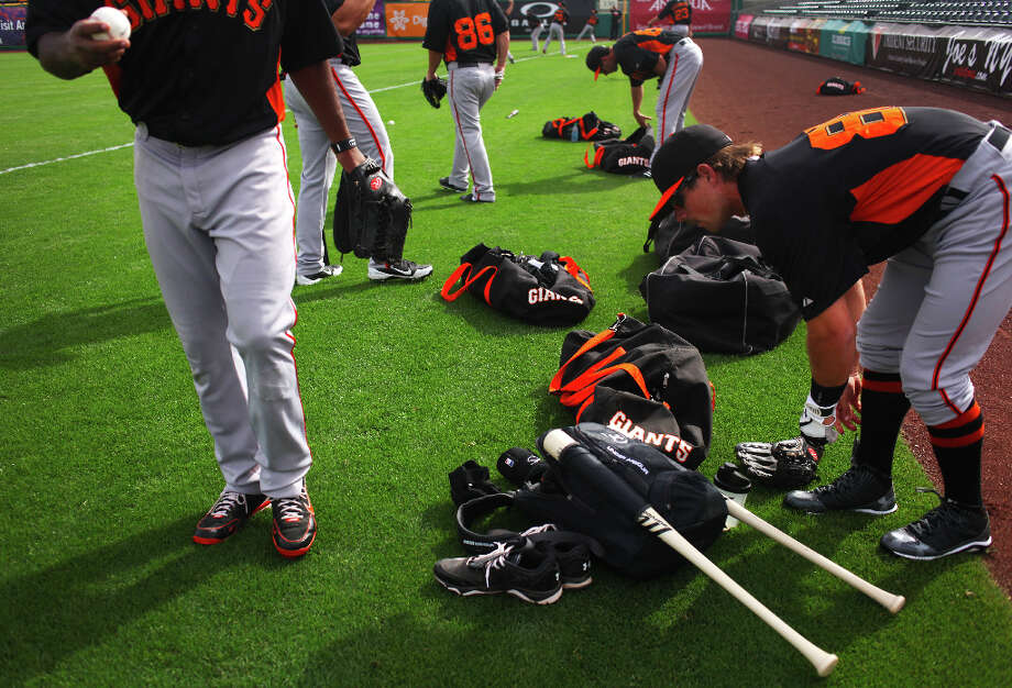 Ryan Cavan, right, tightens his shoelaces as his teammates prepare to warm up at practice on March 20, 2013 in Scottsdale, Arizona. At left, holding a baseball, is Chris Lofton. Photo: Pete Kiehart, The Chronicle / ONLINE_YES