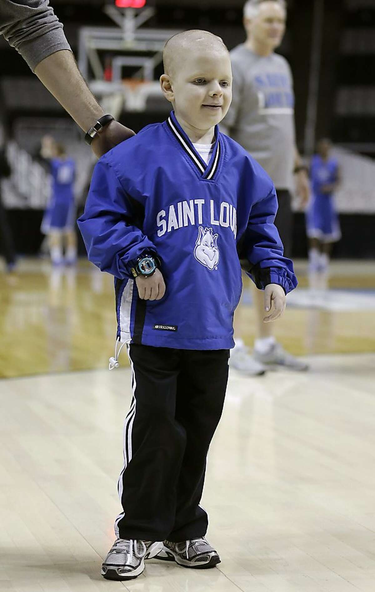 Saint Louis fan Joshua Brown, 9, who has a brain tumor, watches as Saint Louis practice for a second-round game in San Jose, Calif., Wednesday, March 20, 2013.