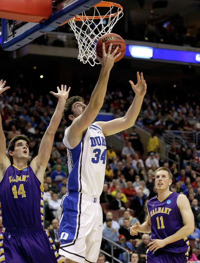 PHILADELPHIA, PA - MARCH 22:  Ryan Kelly #34 of the Duke Blue Devils goes up for a shot against John Puk #44 and Luke Devlin #11 of the Albany Great Danes in the first half during the second round of the 2013 NCAA Men's Basketball Tournament on March 22, 2013 at Wells Fargo Center in Philadelphia, Pennsylvania. Photo: Rob Carr, Getty Images / 2013 Getty Images