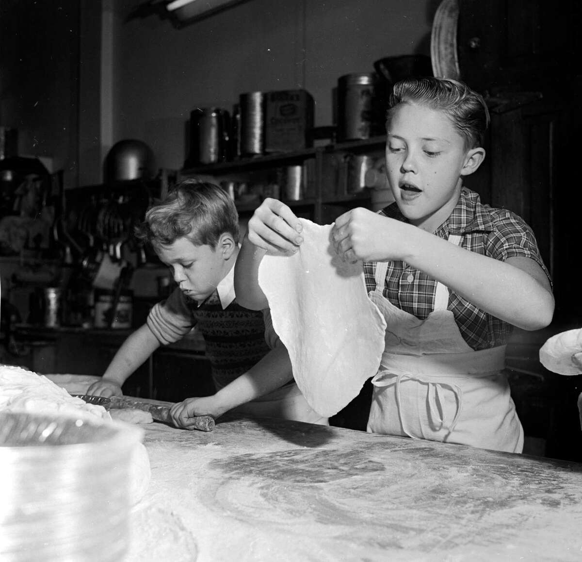 Circa 1955: Young television stars Glenn (left) and Ronnie Walken, later film star Christopher Walken, roll out dough for pie crusts at their father's bakery.