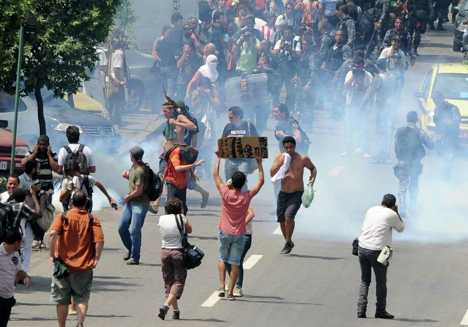 Natives and people who support native cause run as policemen use tear gas as their protest against their eviction from the former Indigenous Museum. Photo: VANDERLEI ALMEIDA, AFP/Getty Images / AFP