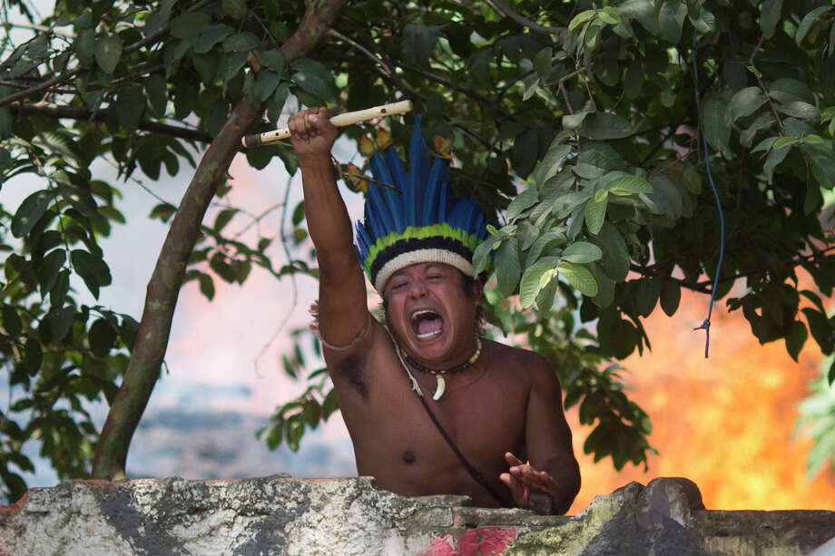 An indigenous man shouts to police, clutching a flute from inside the old Indian Museum where a fire burns behind in Rio de Janeiro. Photo: Felipe Dana, Associated Press / AP