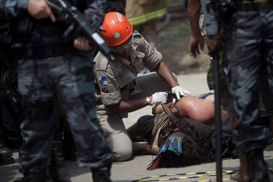 An Indian man laying on the ground receives medical attention after being evicted from the old Indian Museum. Photo: Felipe Dana, Associated Press / AP