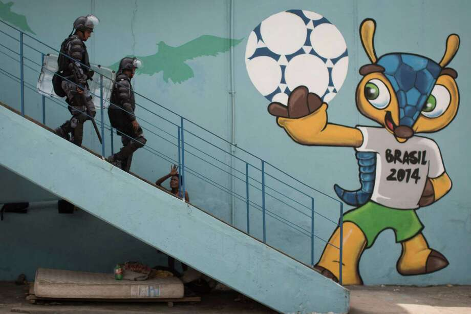 Riot police walk next to a mural of the mascot for the 2014 World Cup soccer tournament, called Fuleco, near the Maracana stadium, after evicting Indians from the nearby old Indian Museum in Rio de Janeiro, Friday, March 22, 2013. Photo: Felipe Dana, Associated Press / AP