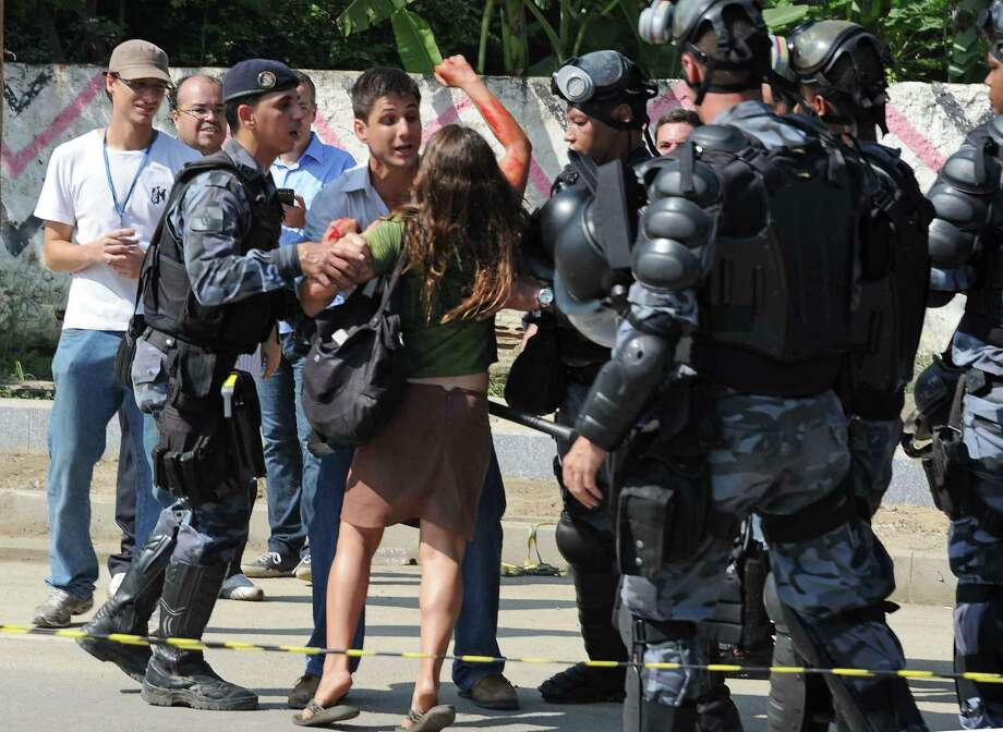 Riot police arrest a demonstrator at the the former Indigenous Museum --aka Aldea Maracana-- next to the Maracana stadium in Rio de Janeiro, Brazil on March 21, 2013. Photo: VANDERLEI ALMEIDA, AFP/Getty Images / AFP