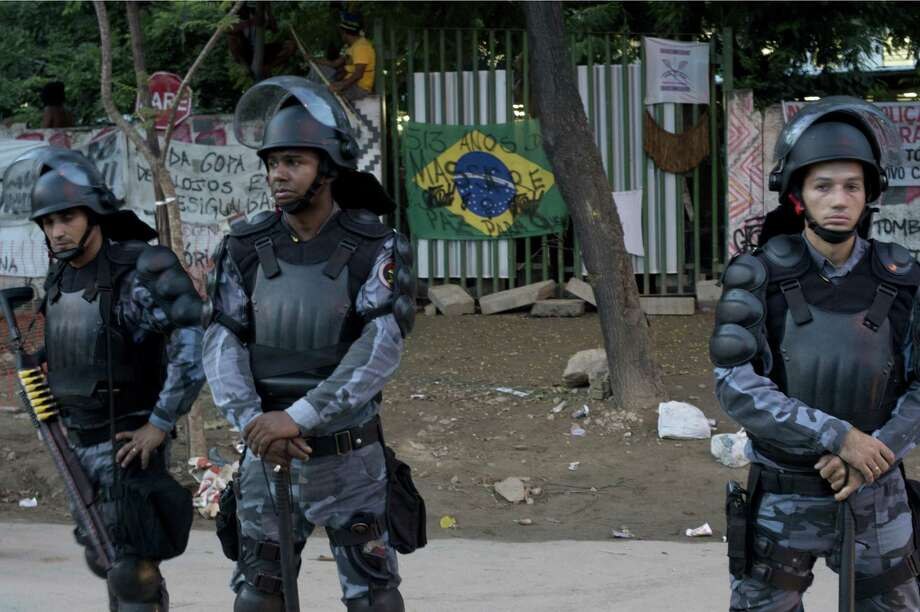 Riot policemen stand guard during the eviction of natives from the former Indigenous Museum, next to the Maracana stadium, in Rio de Janeiro, Brazil on March 21, 2013. Indigenous people have been occupying the place since 2006, which is due to be pulled down to construct a parking lot for the upcoming Brazil 2014 FIFA World Cup. Photo: CHRISTOPHE SIMON, AFP/Getty Images / AFP