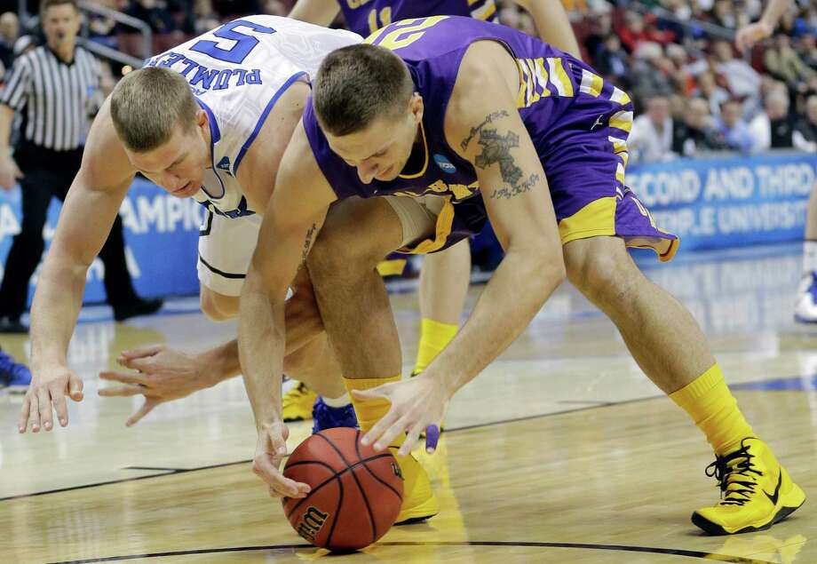 Duke's Mason Plumlee, left, and Albany's Blake Metcalf battle for a loose ball during the first half of a second-round game of the NCAA college basketball tournament, Friday, March 22, 2013, in Philadelphia. Photo: Matt Slocum, AP / AP
