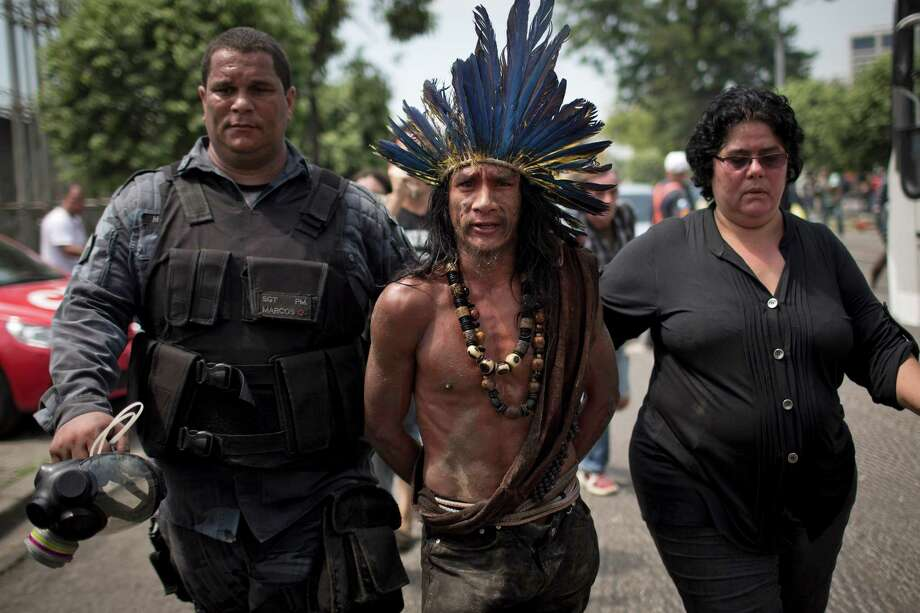 An indigenous man is arrested during clashes outside the old Indian museum, a complex that has been occupied by Indians for years, during an eviction in Rio de Janeiro, Friday, March 22, 2013. Police in riot gear invaded an old Indian museum complex Friday and pulled out a few dozen indigenous people who for months resisted eviction from the building, which will be razed as part of World Cup preparations next to the legendary Maracana football stadium. Photo: Felipe Dana, Associated Press / AP