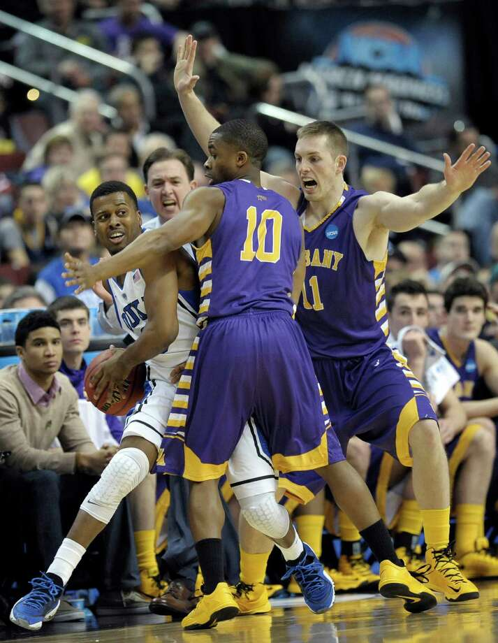 Duke's Tyler Thornton, left, is pressured by Albany's Mike Black, center, and Luke Devlin during the first half of a second-round game of the NCAA college basketball tournament, Friday, March 22, 2013, in Philadelphia. Photo: Michael Perez, AP / FR168006 AP