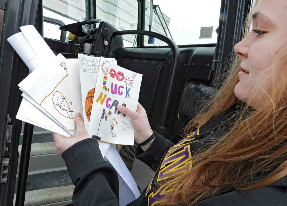 UAlbany basketball player Sarah Royals carries good luck cards hand made by children on to the bus as UAlbany women's basketball team departs from the SEFCU arena for the NCAA Tournament held in Delaware on Friday, March 22, 2013 in Albany, N.Y. (Lori Van Buren / Times Union) Photo: Lori Van Buren