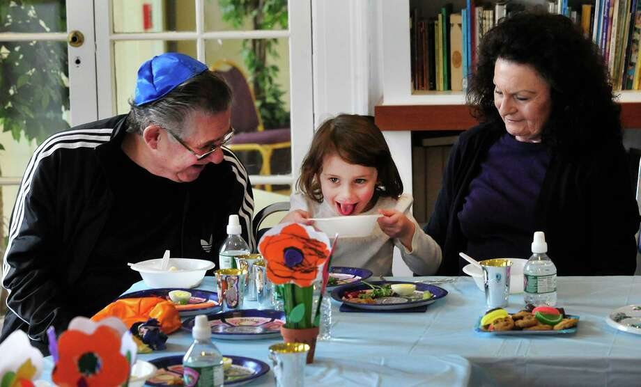 Lily Klotz, 3, licks her bowl as her grandparents, Newton and Gloria Klotz, look on. Students from Maimonides Early Education get ready for Passover with a Seder in Ridgefield, Conn. Friday, March 22, 2013. Photo: Michael Duffy / The News-Times