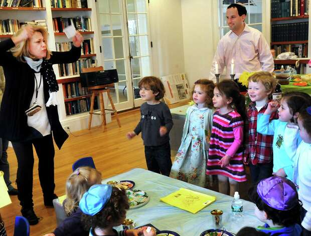 Zina Rosenbaum, left, leads Pre-K students from Maimonides Early Education saying the story of Passover during  a Seder in Ridgefield, Conn. Friday, March 22, 2013. Photo: Michael Duffy / The News-Times