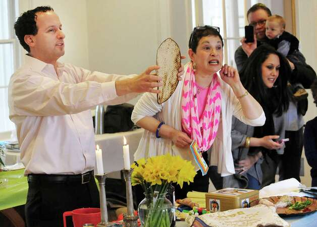 Rabbi Eric Eisenkramer holds up a matza as students from Maimonides Early Education get ready for Passover with a Seder in Ridgefield, Conn. Friday, March 22, 2013. Nursery teacher Talia Gil promps the students to the Rabbi's right. Photo: Michael Duffy / The News-Times