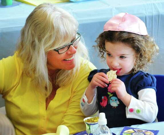 Sophia Bran, 2, eats mataz, while Sharon Vagatti watches as students from Maimonides Early Education get ready for Passover with a Seder in Ridgefield, Conn. Friday, March 22, 2013. Photo: Michael Duffy / The News-Times