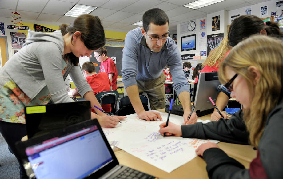 Teacher Joel Pardalis, center, works with students in his sixth-grade language arts class at  New Fairfield Middle School in New Fairfield, Conn. Thursday, March 21, 2013. Photo: Carol Kaliff / The News-Times