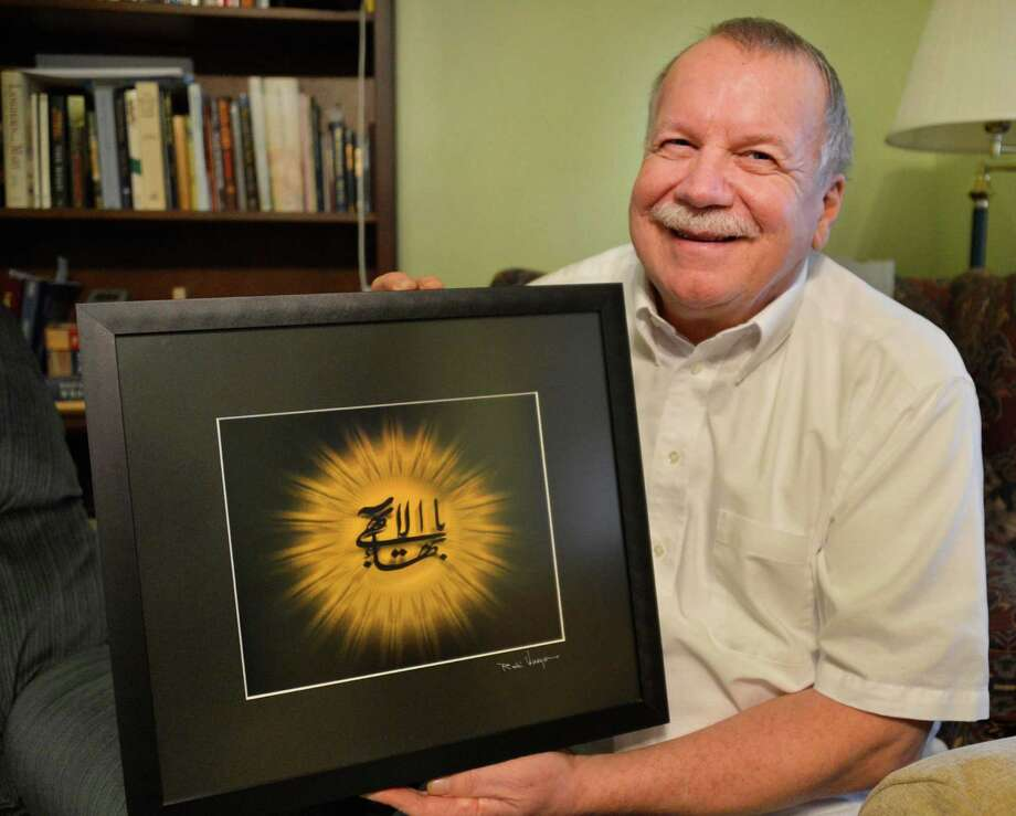 "Paul Murray holds a symbol of the Baha'i faith, a framed Arabic calligraphic rendering known as ""Greatest Name"" at his home in Albany Thursday March 14, 2013.  (John Carl D'Annibale / Times Union) Photo: John Carl D'Annibale / 00021576A"
