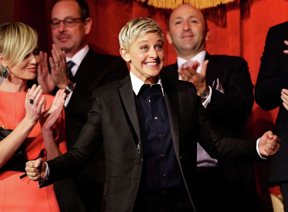FILE - In this Oct. 22, 2012 file photo, Ellen DeGeneres reacts as she is introduced, with wife Portia de Rossi, left, before DeGeneres receives the 15th annual Mark Twain Prize for American Humor at the Kennedy Center in Washington. The talk show host is visiting Sydney and Melbourne on her six-day trip to the country for segments being filmed for her popular U.S. television show. (AP Photo/Alex Brandon, File) Photo: Alex Brandon