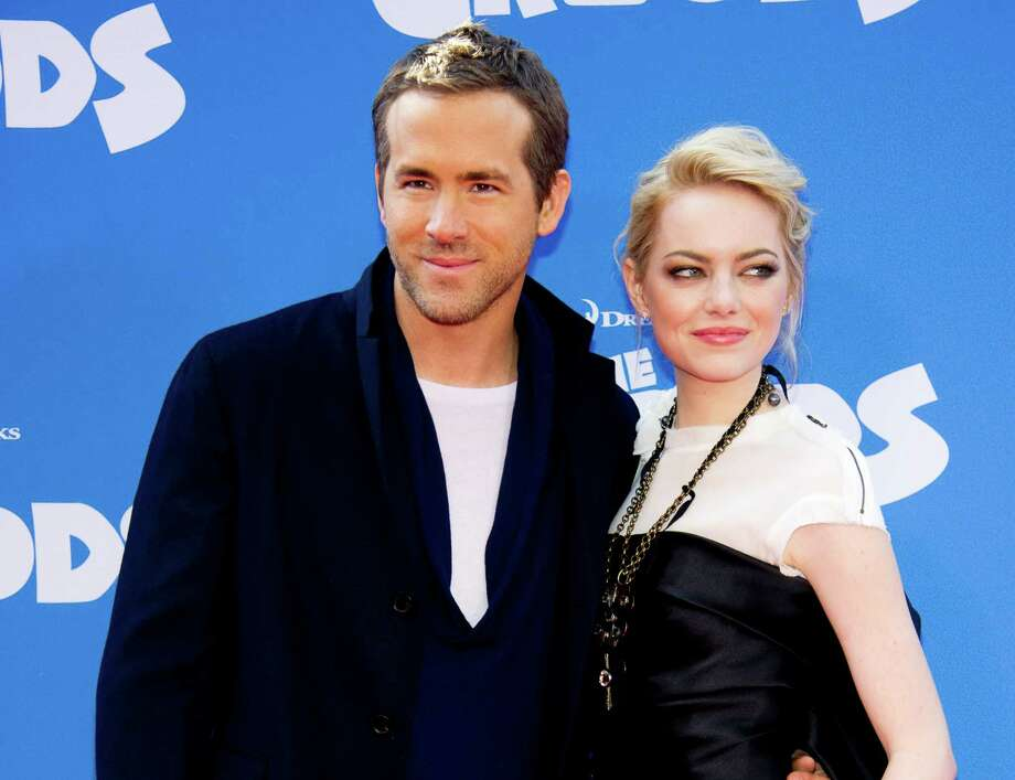 "FILE - This March 10, 2013 file photo shows actors Ryan Reynolds, left, and Emma Stone at ""The Croods"" premiere in New York. Reynolds voices the character Guy and Stone voices the character Eep in the Dreamworks Animation film. (Photo by Charles Sykes/Invision/AP) Photo: Charles Sykes"