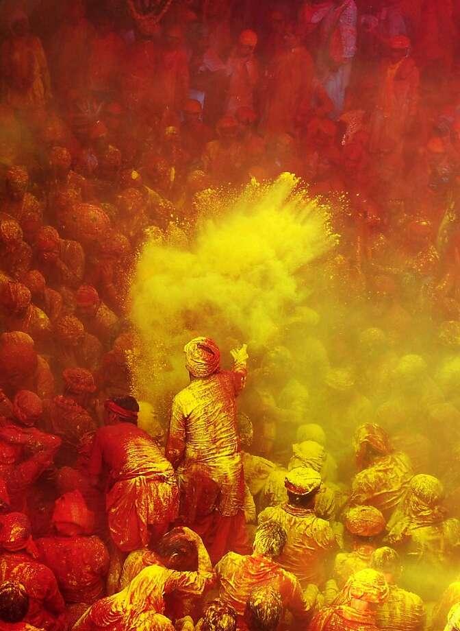 Oh, Holi night:Hindu devotees throw colored powder at Radha Rani temple during the Lathmar Holi festival in Barsana, India. Photo: Sanjay Kanojia, AFP/Getty Images