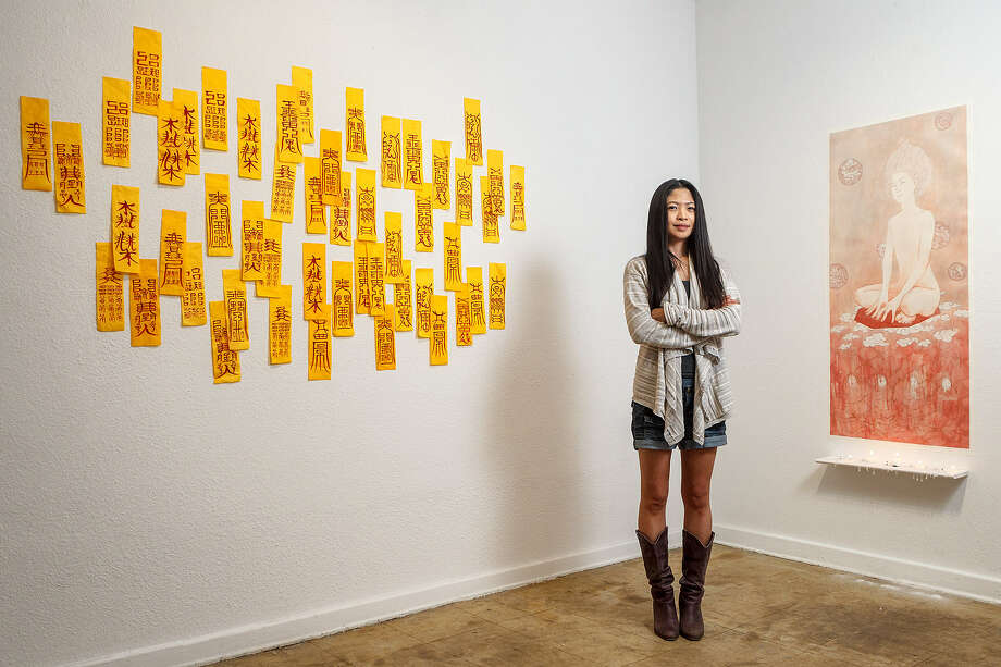 "Jung-hee Mun with artwork titled ""Red Writings, 2013"" (left) and ""on Lines, 2013,"" in her Fl!GHT Gallery exhibit. Photo: Marvin Pfeiffer / San Antonio Express-News"